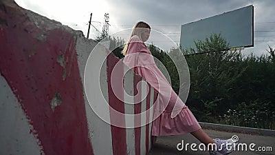 Una ragazza in abito rosa siede su un blocco di calcestruzzo, un cartellone vuoto sullo sfondo stock footage
