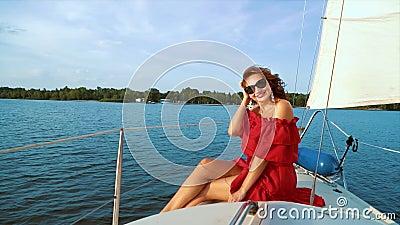 Una ragazza adorabile vestita di rosso e occhiali da sole che si gode l'avventura sulla barca a vela video d archivio