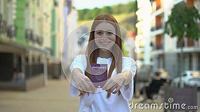 Una ragazza allegra che mostra il passaporto internazionale alla telecamera, opportunità di viaggio video d archivio