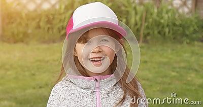 Una ragazza carina e felice con un cappello da camionista che sorride e guarda la telecamera mentre sta in giardino d'estate archivi video