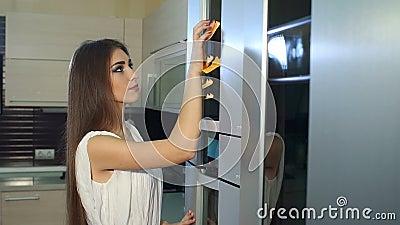 Una ragazza che si avvicina prende una nota dalla porta del frigorifero Movimento lento video d archivio
