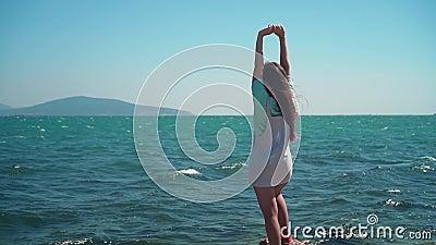 Una ragazza con una T-shirt blu e tute è in piedi vicino al mare La ragazza alza le mani, mostrando un segno di libertà video d archivio