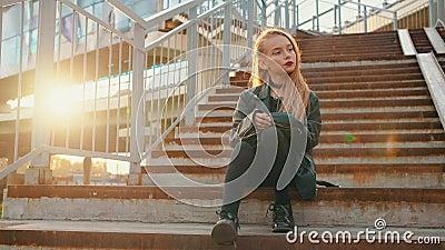 Una ragazza sola con giacca di pelle nera seduta sulle scale al sole Una ragazza attraente con giacca di pelle video d archivio