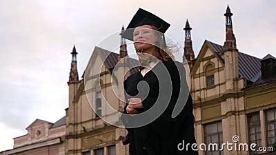Una ragazza sorridente in attesa della cerimonia di laurea video d archivio