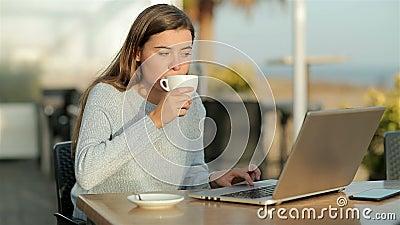 Una ragazza usa il portatile e beve in una caffetteria al rallentatore stock footage