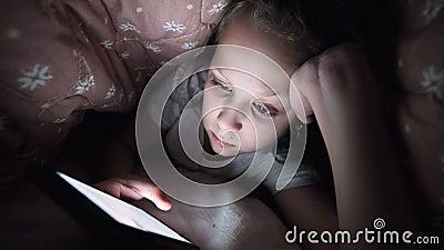 Una ragazzina si nasconde sotto una coperta per usare un dispositivo di smartphone digitale dopo il sonno Solitudine di stock footage