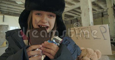 Una senzatetto caucasica sorridente con il volto sporco e gli occhi grigi mangia avidamente la barretta di cioccolato Un piccolo  archivi video