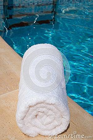 Una toalla blanca enrollada por la piscina azul fotos de for Toallas piscina