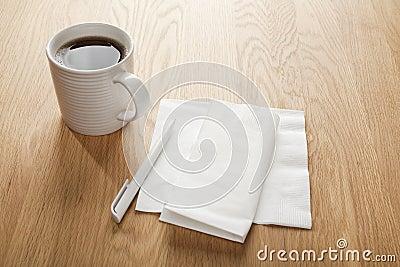 Unbelegte weiße Serviette oder Serviette und Feder und Kaffee