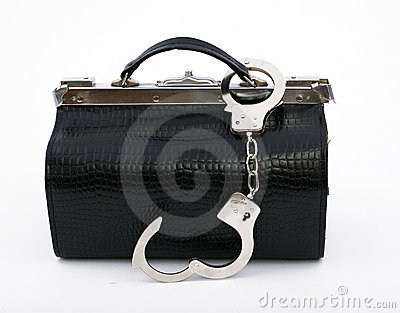 Unbuttoned handcuffs pinned to black leather bag