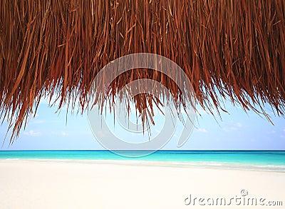 Under a thatched hut at a resort beach
