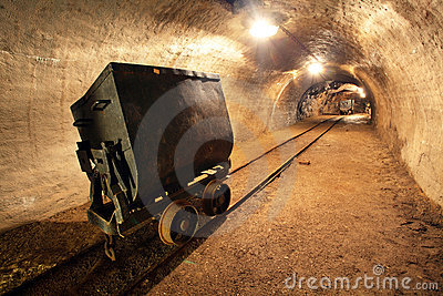 Underground train in mine, carts in gold, silver