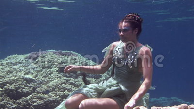 Underwater model free diver poses for camera on background of corals in Red Sea. stock video