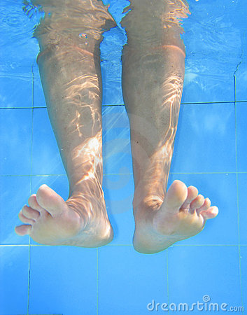 Underwater picture of legs on the swimmingpool.