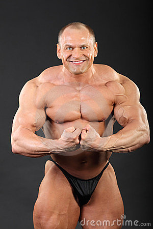 Undressed bodybuilder demonstrates arm muscles