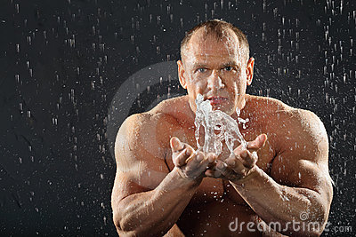 Undressed bodybuilder in rain splashes of water