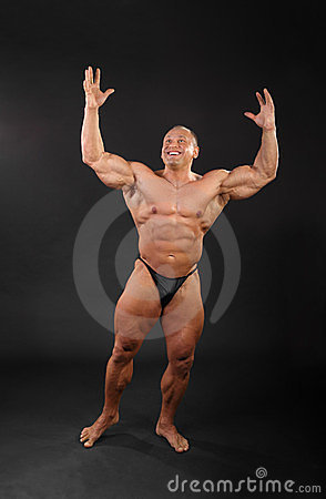 Undressed bodybuilder raises hands up