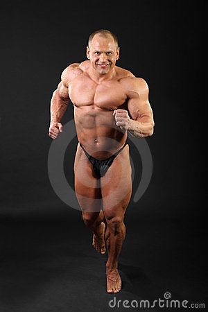 Undressed bodybuilder runs inside studio