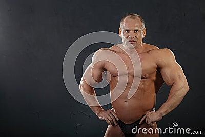 Undressed tanned wet bodybuilder