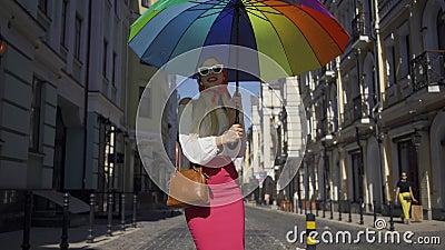 Une belle et positive jeune femme qui marche dans la rue, tournant et regardant l'appareil photo tenant un parapluie multicolore clips vidéos