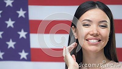 Une belle jeune femme souriante caméra sur fond de drapeau américain, patriotisme banque de vidéos
