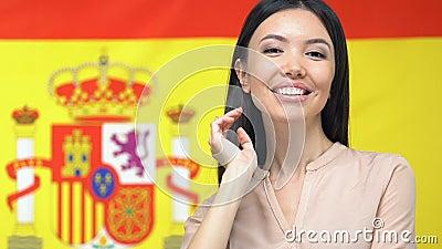 Une belle jeune femme souriante caméra sur fond de drapeau espagnol, patriotisme clips vidéos