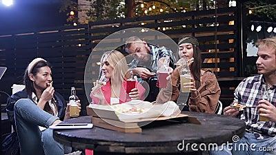 Une belle photo de jeunes gens joyeux et heureux qui s'amusent ensemble pendant la fête avec pizza et boissons en clips vidéos