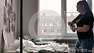 Une brune dans un T-shirt noir et des jeans dessine sur la veste une illustration d'un bull-terrier près de la fenêtre Il y a bea clips vidéos