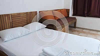 Une chambre d'hôtel avec un double lit blanc, sofa brun avec les coussins oranges et rideaux en chocolat clips vidéos