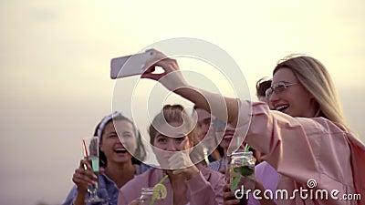 Une compagnie joyeuse et joyeuse d'amis boit des cocktails et prend des selfies au téléphone. cocktail urbain d'été banque de vidéos