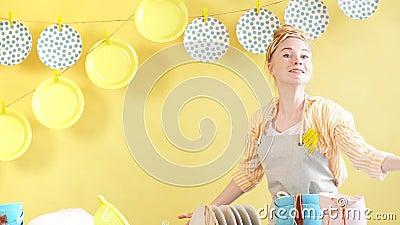 Une domestique active dans des gants et un tablier gris tenant une plaque et regardant la caméra clips vidéos
