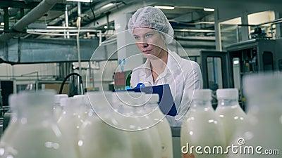 Une employée inspecte le processus de production laitière dans une usine alimentaire banque de vidéos