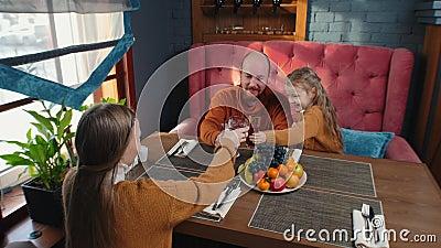 Une famille assise dans le restaurant de l'hôtel accueille ses clients avec des boissons sans alcool banque de vidéos