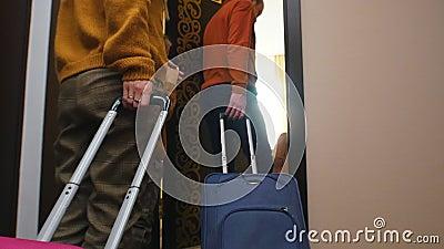 Une famille entre dans une chambre d'hôtel - traînant ses bagages après eux banque de vidéos