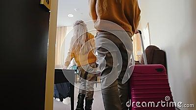 Une famille entre dans une chambre d'hôtel - traînant ses bagages colorés après eux banque de vidéos