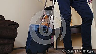 Une famille entre dans une chambre d'hôtel, traînant ses bagages et surveillant banque de vidéos