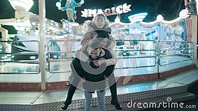 Une famille gaie a l'amusement dans le parc avec des attractions Un homme ramène son épouse et fille sur le sien banque de vidéos