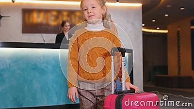 Une famille s'enregistrant dans l'hôtel - une fille tenant ses bagages pendant que sa mère se tenait à la réception banque de vidéos