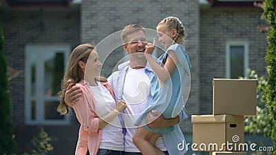 Une famille souriante en train de se faufiler, heureuse de déménager à la maison, prêt à taux d'intérêt bas clips vidéos