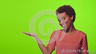 Une femme africaine lève la palme près de l'épaule, tient un espace de copie, sourit, clé chromatique clips vidéos