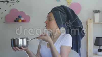 Une femme avec une serviette sur la tête attrape des gouttes d'eau du plafond avec une casserole en métal clips vidéos