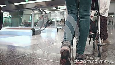 Une femme avec une voiturette à bagages se promène au terminal de l'aéroport banque de vidéos
