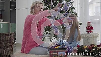 Une femme blanche et une brunette assise par terre devant l'arbre du Nouvel An et choisissant des guirlandes Mère et clips vidéos