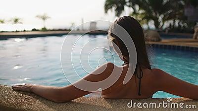 Une femme caucasienne se relaxant dans la piscine du complexe banque de vidéos