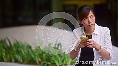Une femme chinoise en chemise blanche à Pékin est assise sur un banc dans un centre commercial banque de vidéos