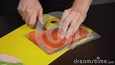Une femme découpe du poisson sur la table closeup clips vidéos
