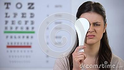 Une femme déprimée fermant l'oeil et tremblant la tête, souffrant d'une mauvaise vision, de mauvais résultats banque de vidéos