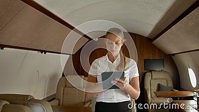 Une femme d'affaires dans un jet surf privé à air sur un tablet PC clips vidéos