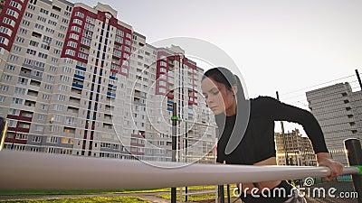Une femme en forme de triceps trempe dans les bars parallèles du parc en faisant de l'exercice à l'extérieur banque de vidéos
