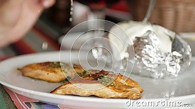Une femme mange du saumon grillé rouge accompagné de pommes de terre La fillette fourre le poisson avec du jus de citron et du se clips vidéos